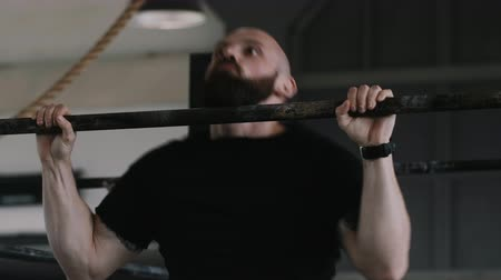 overcome : Close-up muscular young handsome Caucasian man doing chin-up exercises during extreme workout in large gym slow motion.