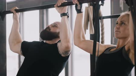 герой : Close-up young happy fit Caucasian man and woman doing chin-ups together. Exercising with personal fitness coach.