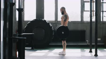 overcome : Side view young Caucasian weightlifting athlete man working out with barbell weight in gym hall. Growth and motivation.