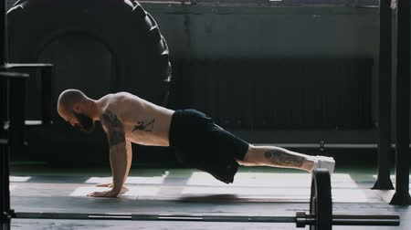 overcome : Wide shot of young Caucasian bearded muscular athlete man doing push-up exercises in large gym hall. Motivation concept.