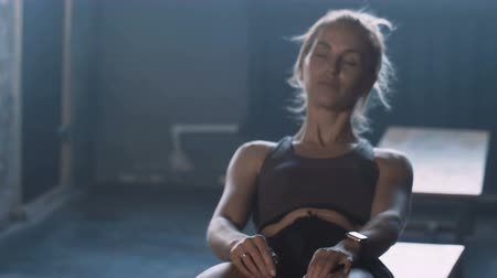 locker : Young beautiful blonde athlete woman lying down alone in dark gym locker room, feeling lost and stressed under pressure.