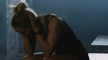 willpower : Attractive sporty blonde woman entering dark gym locker room, sitting down to reflect and overcome stress slow motion.