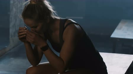 locker : Beautiful athletic European woman entering dark gym locker room, sitting down tired, dealing with failure slow motion.