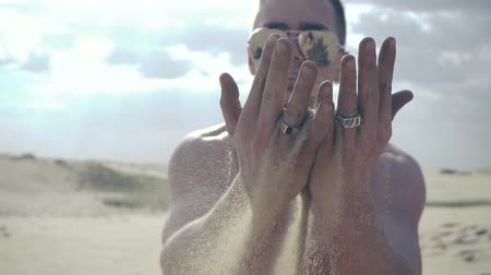 metaphors : Man pours sand through his fingers