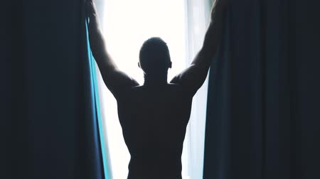 abridor : Man opens the curtains in the morning