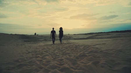 életmód : Couple walking in desert at sunset