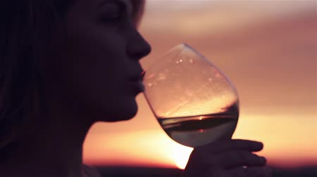 siluety : Beautiful woman with a glass of white wine at sunset