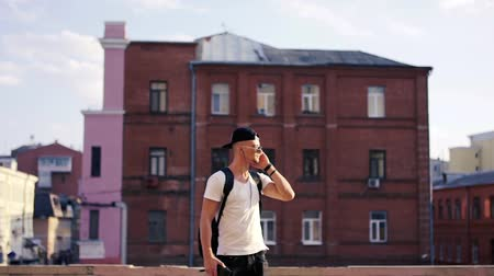 hudební : Young man dancing in headphones in the city