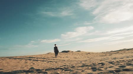 Young beautiful woman walking in desert landscape Wideo