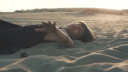 Woman lying on the sand at sunset