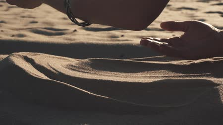 Womans hand touching sand on beach Stock Footage