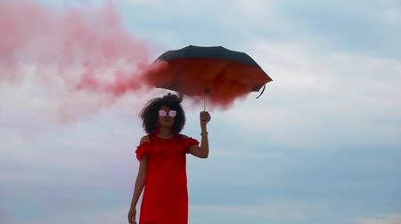 Woman with umbrella in red smoke