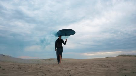 desert life : Woman walking with umbrella with blue smoke