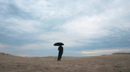 desert life : Woman walking in desert with umbrella