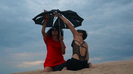 Two women with umbrella on the beach 動画素材