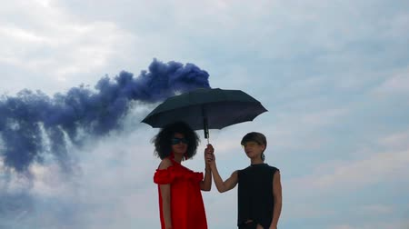 Two women with umbrella in color smoke on the beach