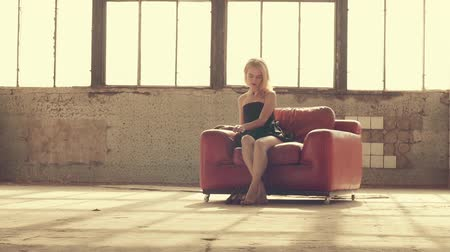 divas : Woman in a red chair in the rays of light