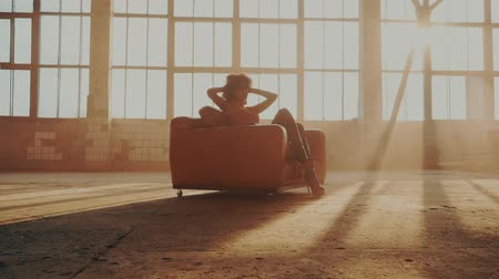 divas : Woman sits in a red chair in the rays of light