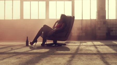 divas : Sexy woman sits in a chair in the rays of light