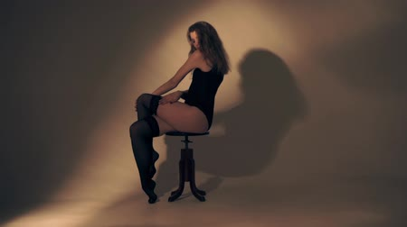по уходу за кожей : Beautiful woman woman sitting on a chair in stockings Стоковые видеозаписи