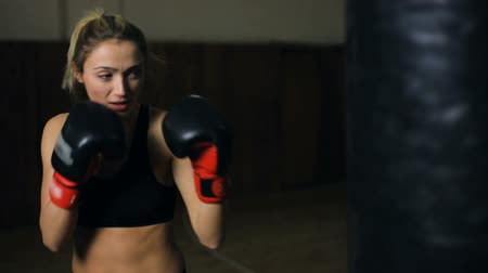 puncs : Young brunette woman in boxing gloves training with a punching bag in a boxing club. Stock mozgókép
