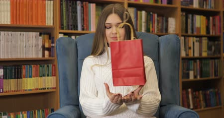kap : Brown-haired young women get a present, gift in white sweater on blue armchair, library background. Valentines Day.