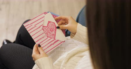 canteiro de flores : Brown-haired young women get valentines card, letter in white sweater on blue armchair, library background. Valentines Day. Vídeos