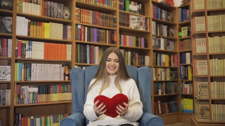 chester : Brown-haired young women in love, fell in love, throw up a plush heart in white sweater on blue armchair, library background. Valentines Day