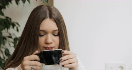 латте : Brown-haired young women portrait in white sweater drink coffee in the cafe. Green zone background.