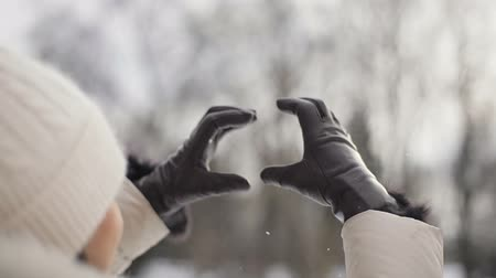 só as mulheres jovens : Brunette young women with pink lips in beige down coat and hat making the symbol of love, heart with her hands in brown gloves against rising morning sun in snowy central park, slow motion. Back view