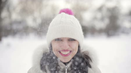 brasão : Closeup Brunette hair young women portrait with pink lips in beige down coat and hat throws up snow and smiling in snowy central park, snowfall. Slow motion. Stock Footage