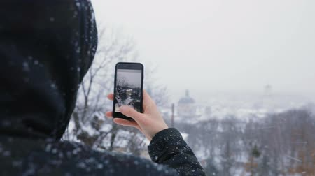 great story : Man in black hood use phone are showing great view of old city town and snowy winter park. Slow motion Stock Footage