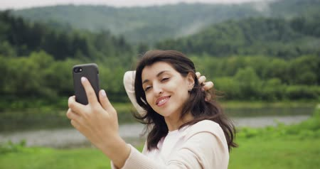 make photo : Brunette young women make selfie photo in the mountains near the river.