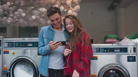 york : Beautiful couple in a laundry listen to the music on the phone, watching videos, stories. Handsome young man with stylish hairсut in jeans shirt. Woman with curly red hair in tartan shirt.