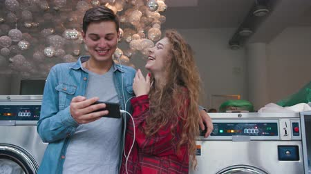 żyrandol : Beautiful couple in a laundry listen to the music on the phone, watching funny videos, stories. Handsome young man with stylish hairсut in jeans shirt. Woman with curly red hair in tartan shirt.