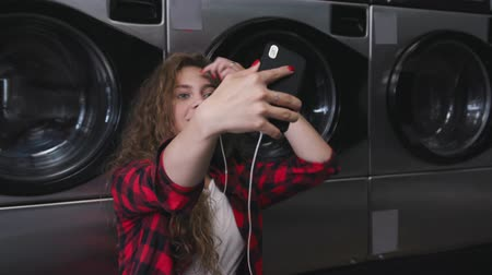 lavatrici : Young beautiful woman with red curly hair in red tartain shirt. Listen to the music, talking by phone. Dance in Laundry. Slow motion Filmati Stock