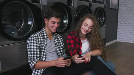 csillár : Beautiful couple in a laundry listen to the music on the phone, watching videos, stories. Handsome young man with stylish hairсut in jeans shirt. Woman with curly red hair in tartain shirt.