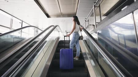 utas : Young brunette woman goes on escalator with travel bag.