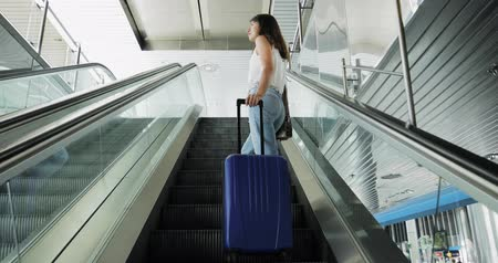 utas : Young beautiful brunette woman goes on escalator in airport with travel bag.