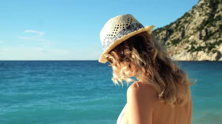 шляпа : Young beautiful girl in hat and sunglasses standing on beach at sunset