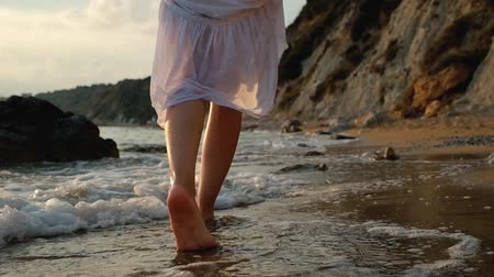 boso : Young woman in white dress walking on a beach