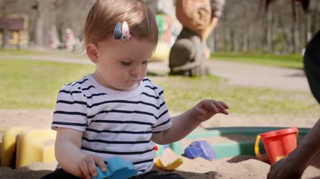lánya : Cute little baby girl playing with her toys sitting in a sandbox at a playground.