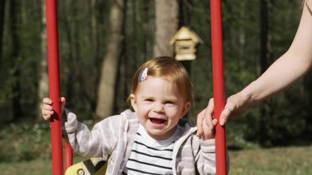 lánya : Cute smiling little baby girl swinging on a swing in the summer day. Slow motion. Stock mozgókép