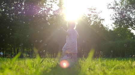 boso : Little baby girl catching on green grass in summer. Slow Motion 120 fps, Happy childhood and Parenthood concept.