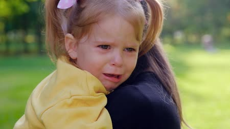 crying baby : Cose-up portrait of a beautiful little two-year-old girl crying in her mothers arms while walking. Baby Care Concept. Full hd 1080 footage