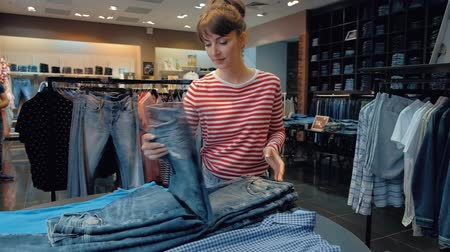 vendedora : Young female seller in a denim store flips through a stack of denim pants during the sales season. Concept of work in a luxury clothing store. Full hd 1080 footage