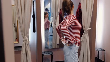 atualizar : Charming young woman tries on stylish denim jeans and looks in the mirrors of a denim fitting room. Wardrobe update concept. Full hd 1080 footage