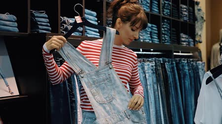 продавщица : Rear view of a pretty young woman in casual wear trying on things in a wardrobe room. Shopping mall concept on weekends and on sales days. Full hd 1080 footage Стоковые видеозаписи