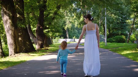 hátsó megvilágítású : Rear view of a young mother in a long white sundress walks with her charming daughter in a blue suit in the park on a sunny warm summer day. The concept of family time and education. 4k footage Stock mozgókép