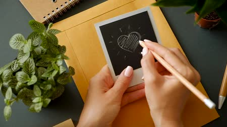 Closeup of the hand of a young girl with a beautiful manicure draw a heart on photo paper over a table with a postal envelope and office supplies. The concept of a message to her boyfriend. Wideo